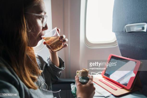 Millennial woman travelling alone in plane.