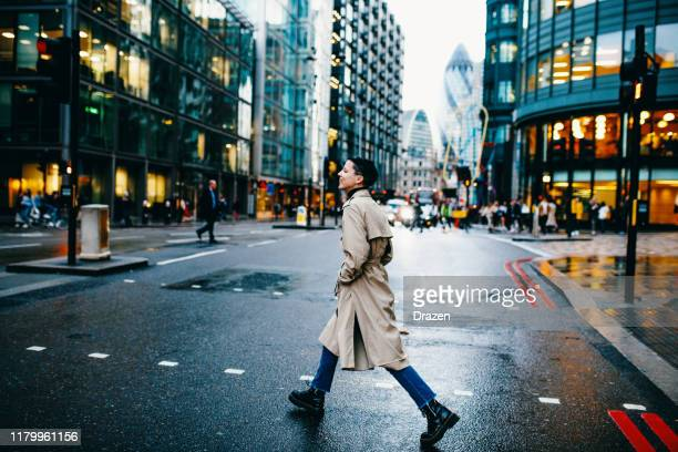 millennial woman with short hair crossing the street on rainy day - central london stock pictures, royalty-free photos & images