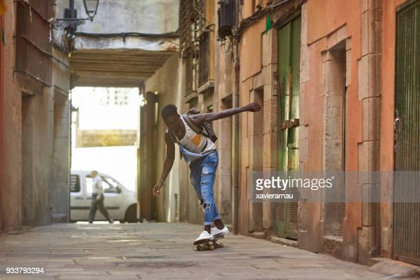 Millennial young African man with skatingboarding around the city