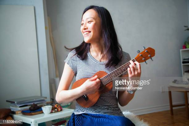 millennial young asian woman having fun playing ukulele in her studio apartment - ukulele stock pictures, royalty-free photos & images