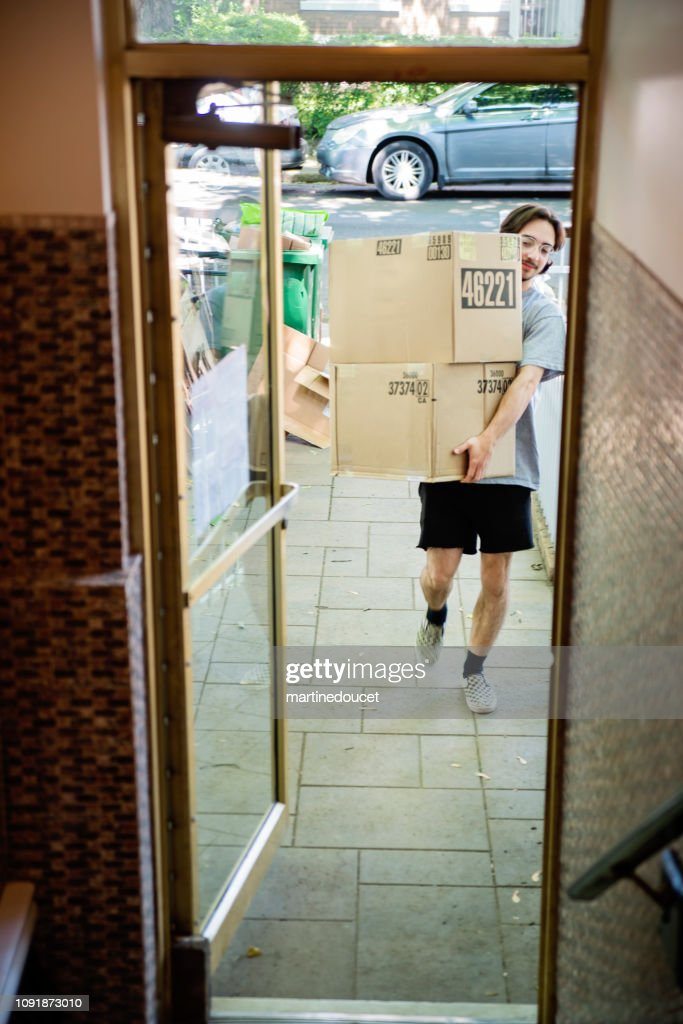 Millennial young man moving in new apartment. : Stock Photo