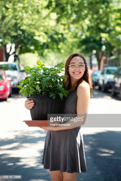 Millennial young woman moving a plant in new apartment.