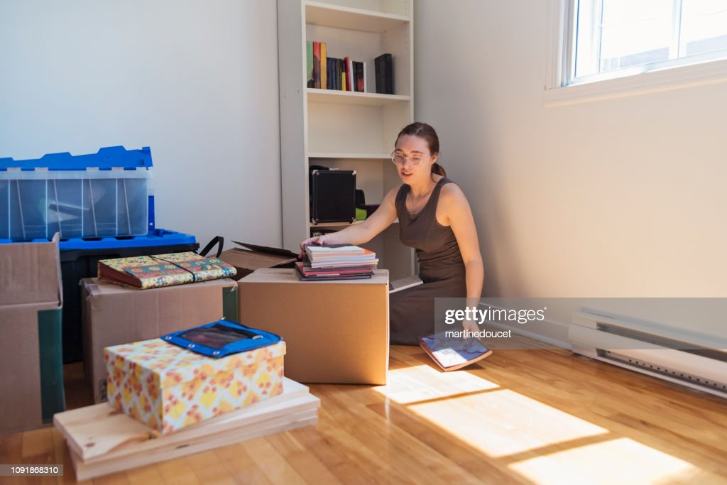 Millennial young woman moving in new apartment. : Stock Photo
