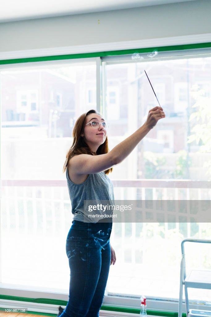 Millennial young woman purifying new apartment with incense. : Stock Photo