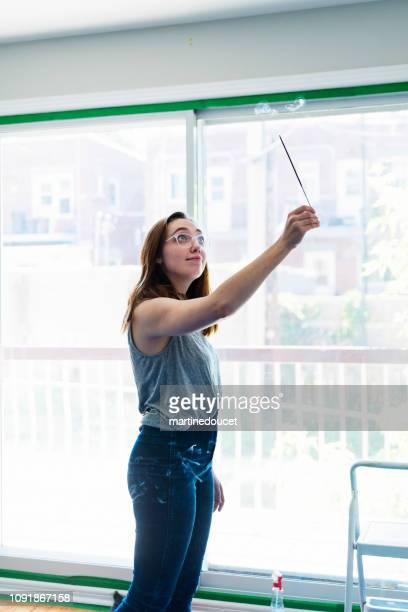 Millennial young woman purifying new apartment with incense.