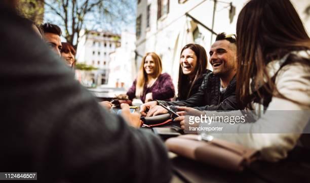 millennials im café mit dem telefon - medium group of people stock-fotos und bilder