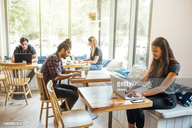 millennials at wifi cafe - wireless technology stock pictures, royalty-free photos & images