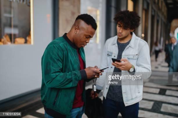 millennials auf der straße mit smartphone - nordafrikanischer abstammung stock-fotos und bilder