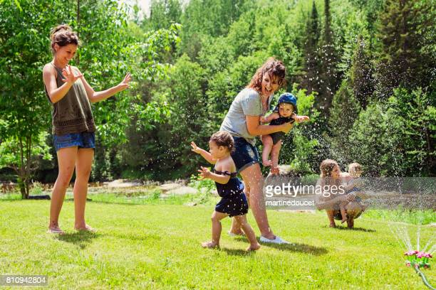 Millennials mothers enjoying springkling water with baby daughters.