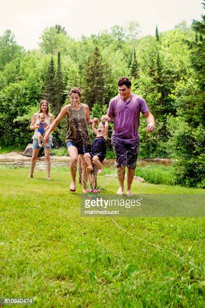 Millennials parents enjoying springkling water with baby daughters.