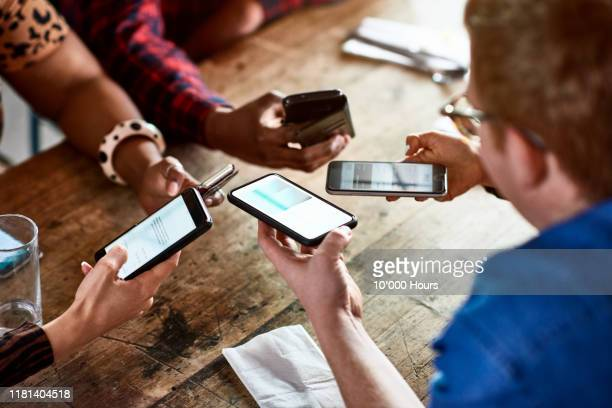 millennials sharing contacts via bluetooth on smartphones - mobile app stock pictures, royalty-free photos & images