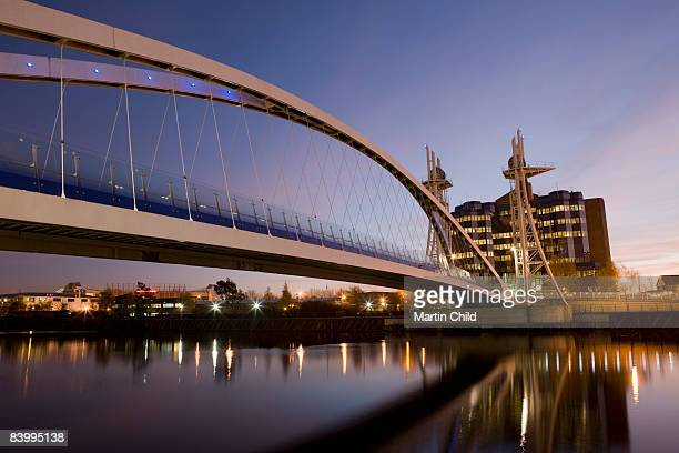 millennium footbridge and office block at dusk - salford stock pictures, royalty-free photos & images