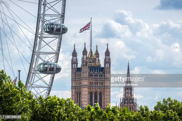 millennium wheel or london eye on the south bank of the river thames in london, england. in the background the victoria tower. - london eye stock pictures, royalty-free photos & images