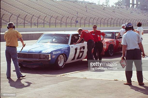 Miller 500 NASCAR Ontario Motor Speedway Mark Donohue of Penske Racing sits near the end of pit lane during qualifying in his AMC Matador talking to...