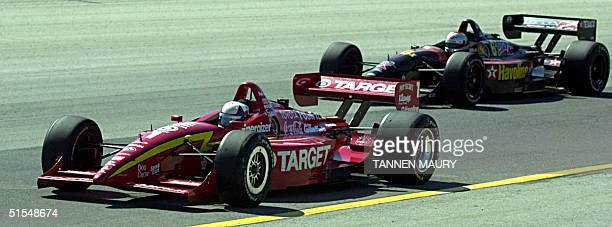 Miller Lite 225 champion Juan Montoya of Colombia, is followed by second place finisher Michael Andretti after taking the checkered flag at the...