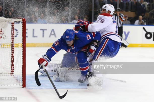 Miller of the New York Rangers gets checked into the goal post by Andrei Markov of the Montreal Canadiens in the second period during Game Four of...