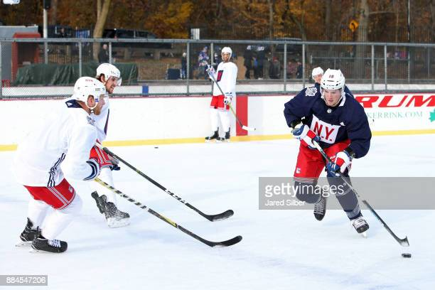 T Miller of the New York Rangers skates with the puck against Steven Kampfer and Brendan Smith during the teams open practice outside at Lasker Rink...