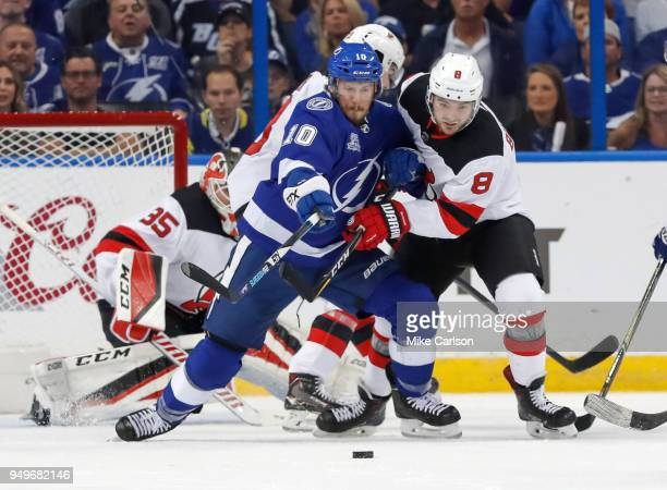 T Miller of the Tampa Bay Lightning battles with Will Butcher of the New Jersey Devils for a loose puck in front of Cory Schneider in the first...