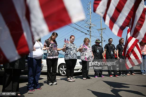 MillerMotte Technical College students and others join in prayer across the highway from the strip mall where a gunman attacked the Armed Forces...