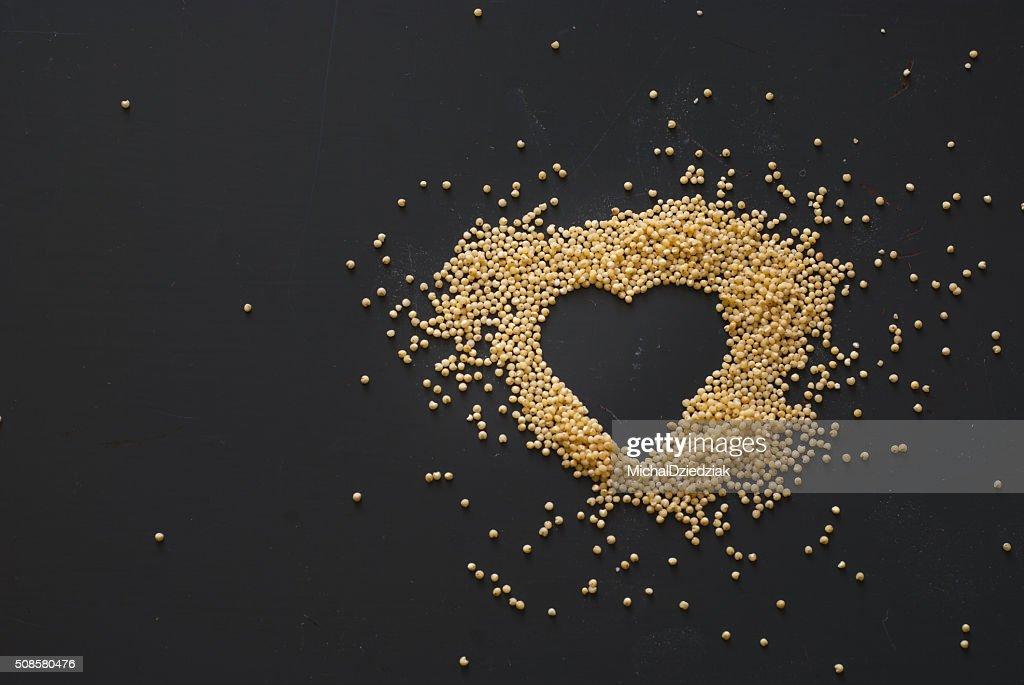 millet heart on dark wooden table : Stock Photo
