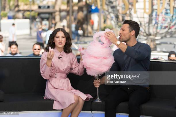 Millie Bobby Brown and Mark Wright eat cotton candy together at 'Extra' at Universal Studios Hollywood on October 27 2017 in Universal City California