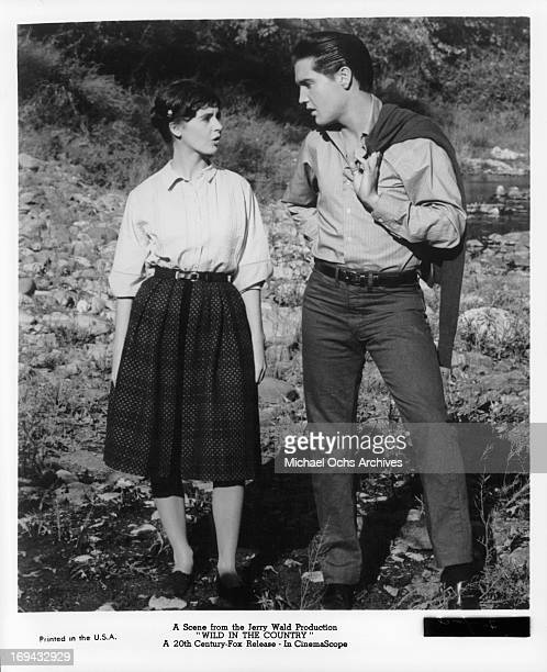 Millie Perkins and Elvis Presley walking outside in a scene from the film 'Wild In The Country' 1961