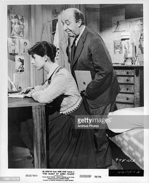 Millie Perkins sits at a desk facing a wall and Joseph Schildkraut stands behind her in a scene from the film 'The Diary Of Anne Frank' 1959