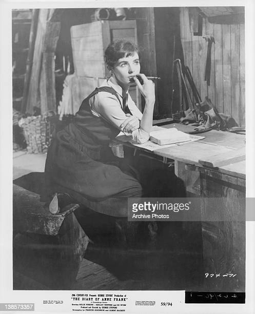 Millie Perkins sits at a desk with a pencil to her chin in a scene from the film 'The Diary Of Anne Frank' 1959