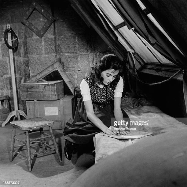 Millie Perkins sits on a bed writing on a tablet of paper in a scene from the film 'The Diary Of Anne Frank' 1959
