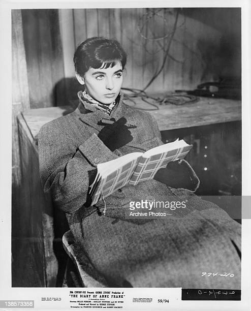 Millie Perkins sitting wearing a coat and gloves holding a journal with a pen in her hand in a scene from the film 'The Diary Of Anne Frank' 1959
