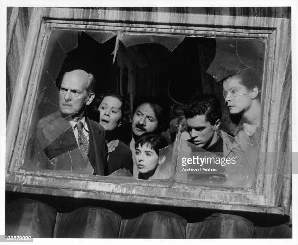 Millie Perkins with a group of unknown actors looking out a broken glass window in a scene from the film 'The Diary Of Anne Frank' 1959
