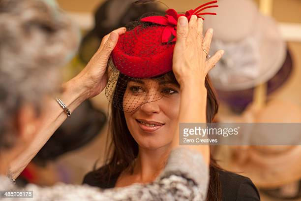 Milliner adjusting hat for customer in shop