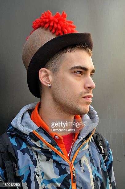 Milliner Jordan Bowen wearing his own punk inspired paisley printed heritage style hat with red cockscomb quiff at London Fashion Week Fall/Winter...