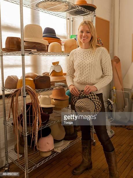 Milliner standing in front of her hat blocks