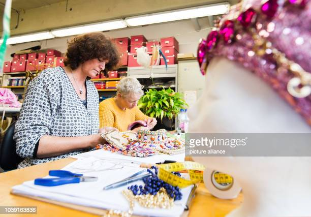 Milliners Claudia Dorn and Susan Pieper decorate hats in the costume workshop for Disney musical Aladdin in Hamburg Germany 3 December 2015 The...