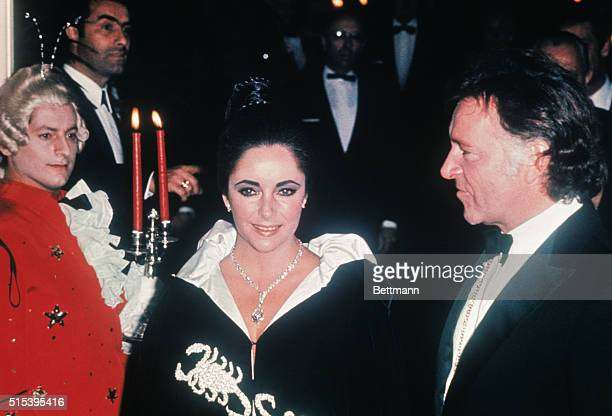 Monte Carlo Liz Taylor positively glows with delight Husband Richard Burton beams happily and at Liz's throat sparkles a diamond worth one million...