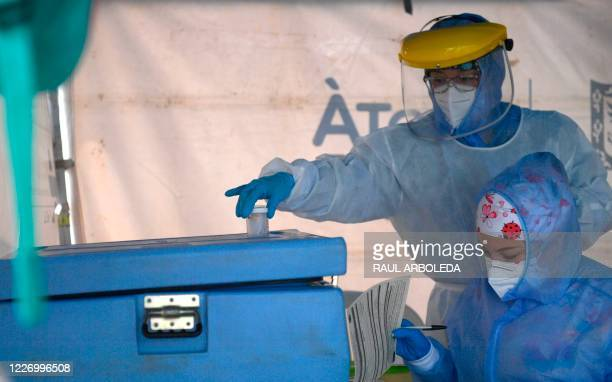 Health workers handle the samples collected from a patient tested for COVID19 coronavirus in Bogota on July 13 2020 Some 35 million people returned...