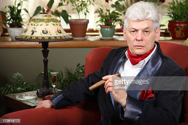 millionaire at home with smoking jacket, cigar, and intense look - millionnaire stock photos and pictures