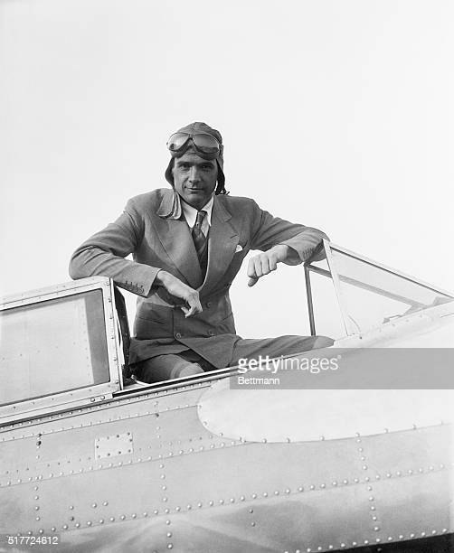 Millionaire Howard Hughes in aviator's gear seated in his plane. Photograph, 1/14/36.