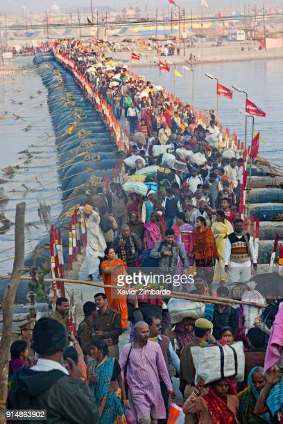 Millions of devotees are crossing daily this footbridge to take a holy dip at the bank of Sangam confluence of rivers Ganga Yamuna and mythical...