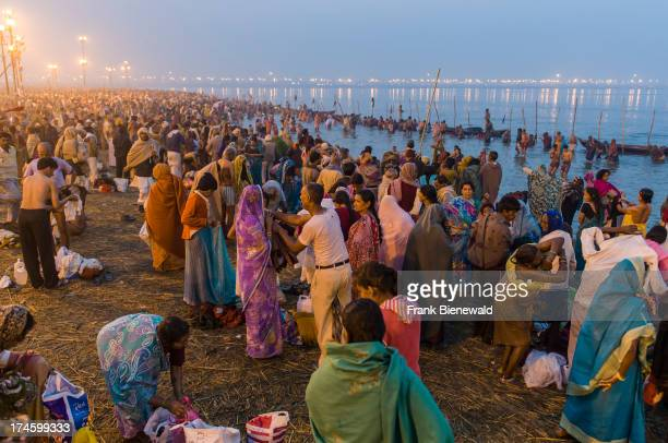 Millions of people gathering early morning at the Sangam the confluence of the rivers Ganges Yamuna and Saraswati for the holy bath at Kumbha Mela