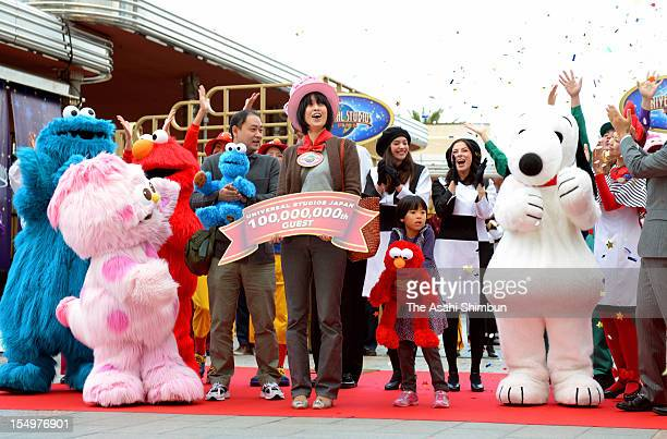 A 100 millionth guest poses for photogrpahs with mascots at Universal Studios Japan on October 28 2012 in Osaka Japan The theme park opened in 2001
