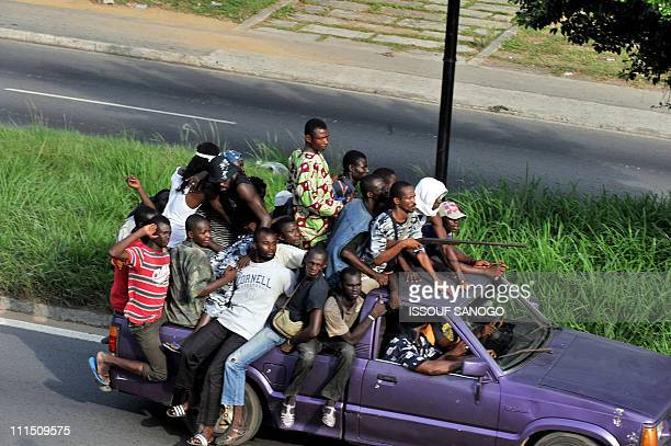 Millitaimen loyal to Alassane Ouattara drive a vehicle along a street in Abidjan on April 1 2011 Ivory Coast strongman Laurent Gbagbo's forces...