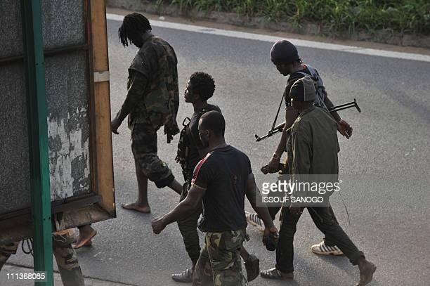 Millitaimen loyal to Alassane Ouattara walk along a street in Abidjan on April 1 2011 Ivory Coast strongman Laurent Gbagbo's forces repulsed an...