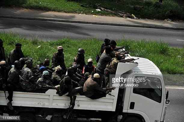 Millitaman loyal to Alassane Ouattara drive in a vehicle along a street in Abidjan on April 1 2011 Ivory Coast strongman Laurent Gbagbo's forces...