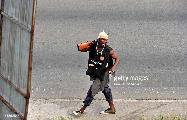 A millitaman loyal to Alassane Ouattara walks along a street in Abidjan on April 1 2011 Ivory Coast strongman Laurent Gbagbo's forces repulsed an...