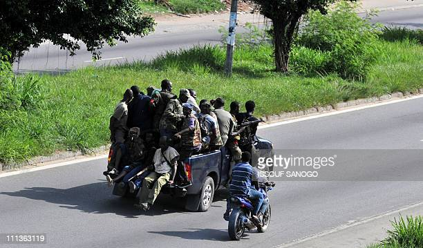 Millitamen loyal to Alassane Ouattara drive a vehicle along a street in Abidjan on April 1 2011 Ivory Coast strongman Laurent Gbagbo's forces...