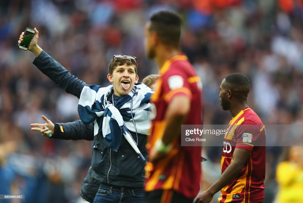 Millwall fans reatc towards Bradford City players as they invade the pitch in celebration after the Sky Bet League One Playoff Final between Bradford City and Millwall at Wembley Stadium on May 20, 2017 in London, England.