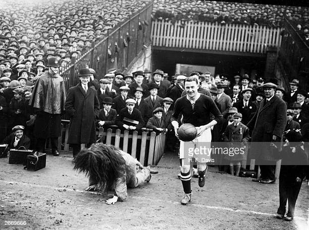 Millwall Football Club captain Len Graham fails to conceal his amusement as he leads his team out at the Den and the mascot a man dressed as a lion...