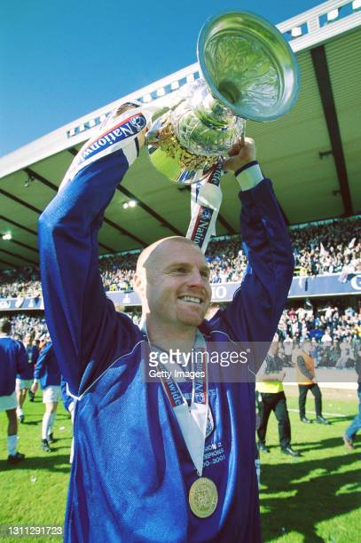 Millwall player Sean Dyche lifts the trophy after Millwall are crowned Division Two champions at the New Den after a game against Oldham Athletic on...
